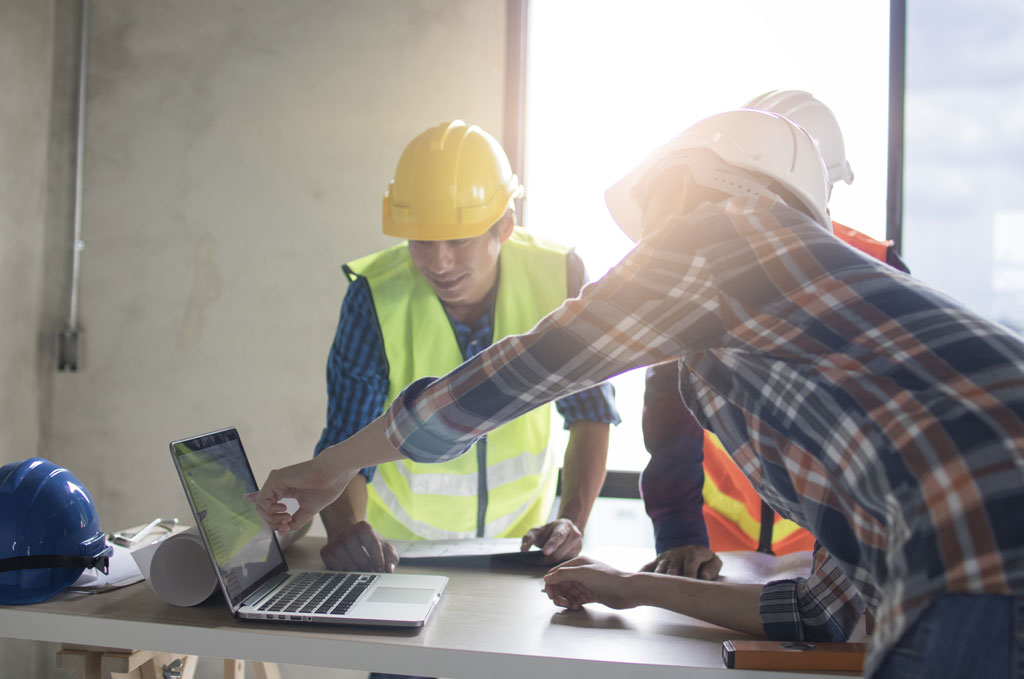 Three construction workers looking and pointing at a laptop